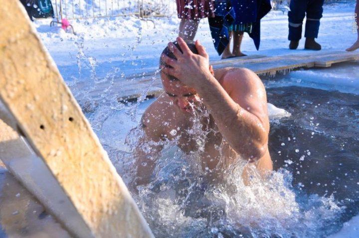 мужчина окунается в холодной воде